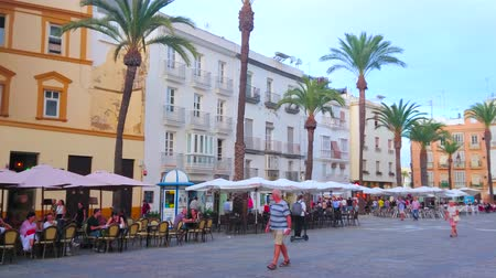 torre : CADIZ, SPAIN - SEPTEMBER 19, 2019: Panorama of crowded Plaza de la Catedral (Cathedral square) with historical edifices, outdoor restauants and medieval stone Cathedral, on September 19 in Cadiz Stock Footage