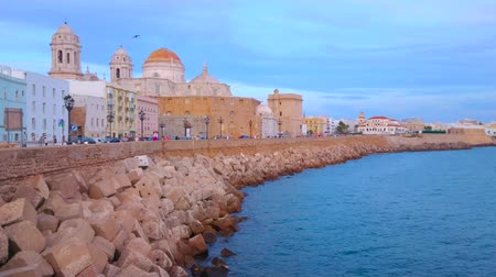 crepúsculo : CADIZ, SPAIN - SEPTEMBER 19, 2019: Evening Campo del Sur avenue with a view on historical housing, rampart, Cathedral, medieval Santa Cruz Church and coast of Atlantic Ocean, on September 19 in Cadiz