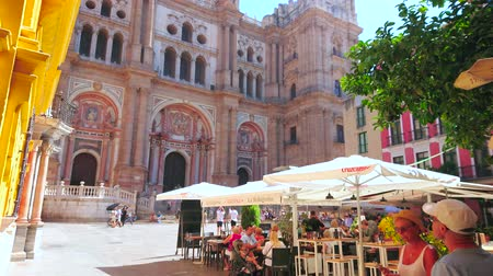 torre : MALAGA, SPAIN - SEPTEMBER 26, 2019: The old Plaza Obispo square is best place to relax in outdoor cafe amid historical landmarks, such as Bishops Palace and Cathedral, on September 26 in Malaga