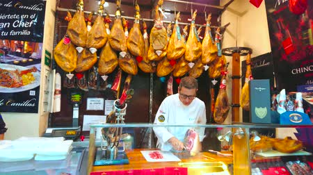 mercado : MALAGA, SPAIN - SEPTEMBER 26, 2019: The process of hand-cutting of Jamon Iberico (dry-cured Spanish ham); the seller carves the slices from the whole jamon leg, on September 26 in Malaga