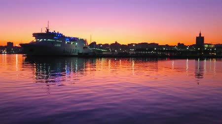 relaks : MALAGA, SPAIN - SEPTEMBER 26, 2019: The ripples on colorful Mediterranean sea surface, reflecting sunset and cruise liner, moored in Malaga Port, on September 26 in Malaga