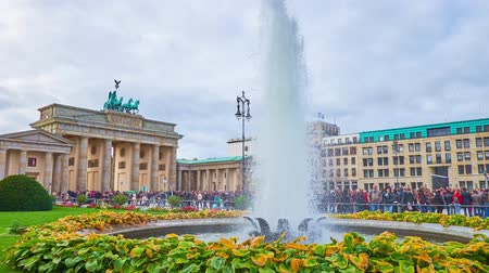 turisták : BERLIN, GERMANY - OCTOBER 3, 2019: The scenic fountain amid the small garden on Pariser Platz with a view on Brandenburg Gate and crowded Unter der Linden avenue on background, on October 3 in Berlin