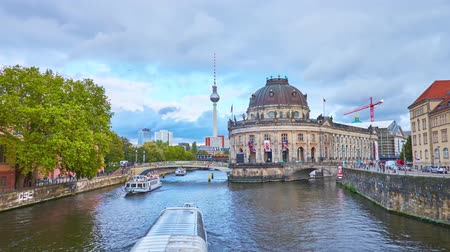 turisták : BERLIN, GERMANY - OCTOBER 3, 2019: The Spree river forks at the Museum Island with impressive Bode Museum building on its end; pleasure boats float in different directions, on October 3 in Berlin