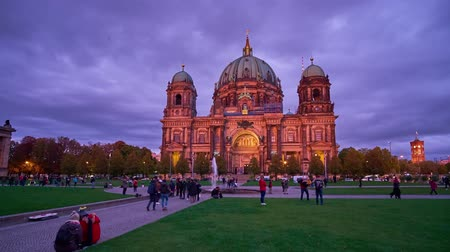 BERLIN, GERMANY - OCTOBER 3, 2019: People walk along Lustgarten park, enjoying magical twilights, fast running cloudsand illumination of Berliner Dom, on October 3 in Berlin