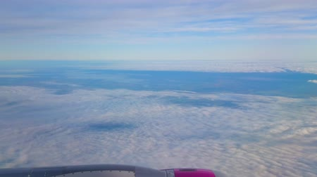 Aerial view from the aircraft on fluffy white clouds, covering the hilly land on territory of Germany
