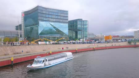 pitka : BERLIN, GERMANY - OCTOBER 3, 2019: The pleasure boats float through the Spree river along the central business district with glass buildings and Hauptbahnhof railway station, on October 3 in Berlin