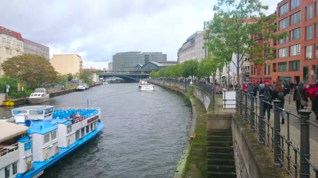 turisták : BERLIN, GERMANY - OCTOBER 3, 2019: Spree river runs through the old district, one of the most visited parts of the city with tourist boats and different style architecture, on October 3 in Berlin