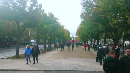 dworek : BERLIN, GERMANY - OCTOBER 3, 2019: People walk along famous central Unter der Linden boulevard in surrounding of the lime trees, that leads to the Brandenburg Gate, on October 3 in Berlin