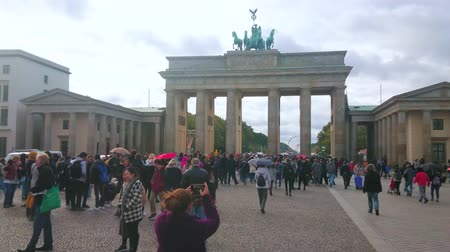 pedestres : BERLIN, GERMANY - OCTOBER 3, 2019: The crowded Unter der Linden avenue on holiday festivities, helding at  Brandenburg Gate during German Unity Day, on October 3 in Berlin