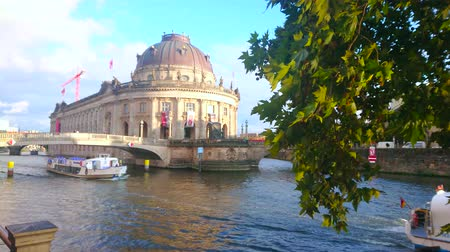 turisták : BERLIN, GERMANY - OCTOBER 3, 2019: The view on Bode Museum, Monbijou bridge, Spree river and floating pleasure boats through the lush green maple branch, swaying on the wind, on October 3 in Berlin