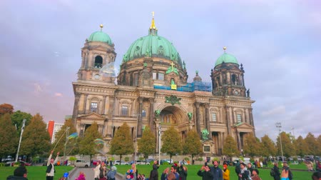 BERLIN, GERMANY - OCTOBER 3, 2019: The kids jump, trying to catch the large flying bubbles, blown out by the street artisan in Lustgarten Park in front of Berliner Dom, on October 3 in Berlin