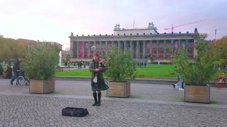 kolumna : BERLIN, GERMANY - OCTOBER 3, 2019: The bagpipe street musician in Highland dress plays at the Lustgarten Park with Altes Museum building on background, on October 3 in Berlin Wideo