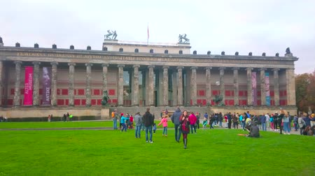 kolumna : BERLIN, GERMANY - OCTOBER 3, 2019: Children play with bubbles on the lawn in front of facade of the Altes (old) Museum with colonnades on its balustrade, on October 3 in Berlin