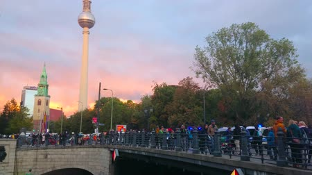 crepúsculo : BERLIN, GERMANY - OCTOBER 3, 2019: People walk through the Karl-Liebknecht bridge with a view on Fernsehturm tower and St Marienkirche church on colorful cloudy sunset, on October 3 in Berlin