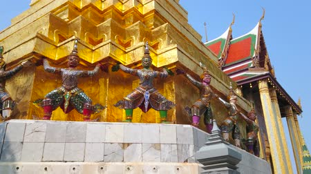 BANGKOK, THAILAND - MAY 12, 2019: The ornate statues of monkeys and demons guard (yaksha), supporting the golden pagoda in Grand Palace, on May 12 in Bangkok