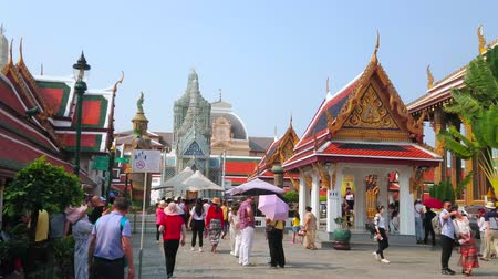 dekorasyon : BANGKOK, THAILAND - MAY 12, 2019: The crowded Grand Palace alley with a view on covered gallery, ornate pavilion and Hor Phra Gandhararat shrine with prang tower, on May 12 in Bangkok Stok Video