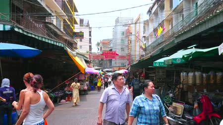 mercado : BANGKOK, THAILAND - MAY 12, 2019: People walk the market streets of Chinatown with small stores, stalls, outdoor cafes, street food sellers, shabby buildings and hotels, on May 12 in Bangkok