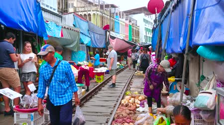 запретить : MAEKLONG, THAILAND - MAY 13, 2019: Maeklong Railway Market (Talad Rom Hoop) boasts wide range of fresh fruits, vegetables, local foods, snacks and souvenirs, on May 13 in Maeklong