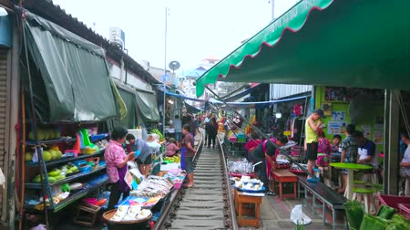 запретить : MAEKLONG, THAILAND - MAY 13, 2019: Maeklong Railway Market is popular among the tourists, visiting it to see the riding train and make some shopping in exotic place, on May 13 in Maeklong