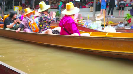 DAMNOEN SADUAK, THAILAND - MAY 13, 2019: The boat of food vendor, selling fruits, seafood and rice, floating along the canal of Ton Khem market, on May 13 in Damnoen Saduak