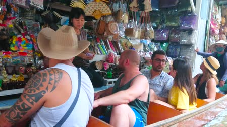 turisták : DAMNOEN SADUAK, THAILAND - MAY 13, 2019: Tourists choose the souvenirs, sitting in a boat at the stall of Ton Khem floating market, on May 13 in Damnoen Saduak Stock mozgókép
