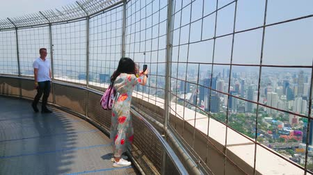 pathum wan : BANGKOK, THAILAND - APRIL 24, 2019: The couple of tourists enjoys the views and makes pictures from rotating observation platform of Baiyoke Tower II, on April 24 in Bangkok Stock Footage