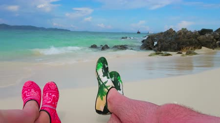 sziget : PHUKET, THAILAND - MAY 1, 2019:Relax on sandy beach of Khai Nok island, enjoy the sunbath, lying on the shore line in aqua shoes, on May 1 in Phuket