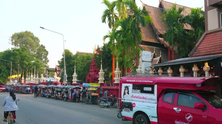 CHIANG MAI, THAILAND - MAY 2, 2019: The road in front of Wat Phantao Temple with line of parked tuk tuks and driving songtaew pickup truck taxi, on May 2 in Chiang Mai Stock Footage