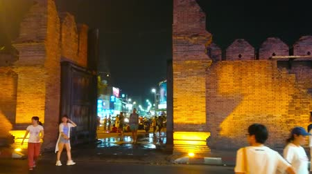 mercado : CHIANG MAI, THAILAND - MAY 2, 2019: The evening view of Tha Pae Gate and ruins of the brick fortress wall with battlements in dimmed lights, on May 2 in Chiang Mai