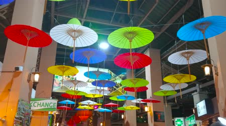 CHIANG MAI, THAILAND - MAY 2, 2019: The ceiling in hall of Kalare Night Market is decorated with colorful Oriental umbrellas installation, on May 2 in Chiang Mai