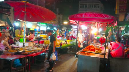 mercado : CHIANG MAI, THAILAND - MAY 2, 2019: People walk the curved narrow alley among the small food stalls of Warorot Night Market, on May 2 in Chiang Mai