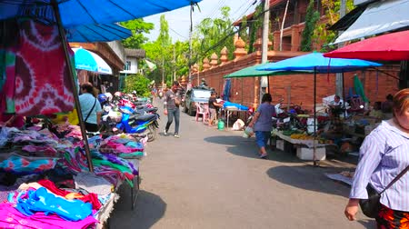 crowded : CHIANG MAI, THAILAND - MAY 4, 2019: The busy Pra Pok Clao road with garment and household stalls of chaotic Gate Market, full of porters, bicycles, mopeds and walking people, on May 4 in Chiang Mai Stock Footage