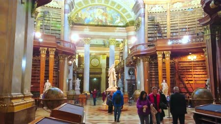 semt : VIENNA, AUSTRIA - MARCH 2, 2019: The Prunksaal of National Library with tourists, walking among the vintage bookcases and slender columns, on March 2 in Vienna Stok Video