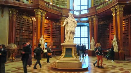 histórico : VIENNA, AUSTRIA - MARCH 2, 2019: The Spectacular hall of Prunksaal of National Library with marble statue of Emperor Charles VI and carved wooden bookcases, on March 2 in Vienna