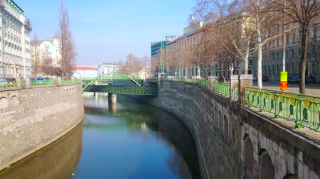 semt : VIENNA, AUSTRIA - FEBRUARY 18, 2019: The stone embankment of Wienfluss river with shady trees and a view on Zollamtsbrucke railway bridge and Zollamtssteg pedestrian bridge, on February 18 in Vienna Stok Video