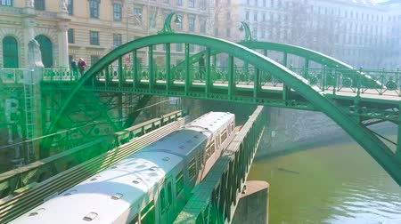 semt : VIENNA, AUSTRIA - FEBRUARY 18, 2019: The bridge complex across Wein River consists of arched Zollamtssteg bridge and lower Zollamtsbrucke with riding U-Bahn train, on February 18 in Vienna, Austria Stok Video