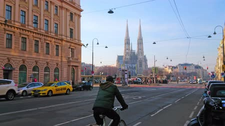 semt : VIENNA, AUSTRIA - FEBRUARY 18, 2019: The busy streets of the old town with fast traffic and neo-gothic Votivkirche (Votive Church) on background, on February 18 in Vienna Stok Video