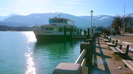 паром : ST WOLFGANG, AUSTRIA - FEBRUARY 23, 2019: Embankment of Wolfgangsee lake with ferry in port and hazy Alps on the background, on February 23 in St Wolfgang
