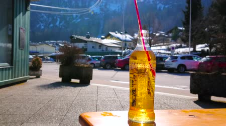 очки : ST GILGEN, AUSTRIA - FEBRUARY 23, 2019: The vintage bottle of fizzy Almdudler soft drink in outdoor cafe with a view on riding cabins of Zwolferhorn cable car, on February 23 in St Gilgen Стоковые видеозаписи