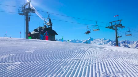 жесткий : ZELL AM SEE, AUSTRIA - FEBRUARY 28, 2019: Enjoy winter landscape of Schmitten mount with corduroy pistes, riding chairlift, Elisabeth chapel and contrail in blue sky, on February 28 in Zell Am See Стоковые видеозаписи