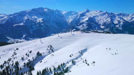 air vehicle : Panorama of Schmittenhohe mount with chairlifts, cableways, fine ski pistes, numerous snowshoeing routes and rocky Alps on background, Zell am See, Austria Stock Footage