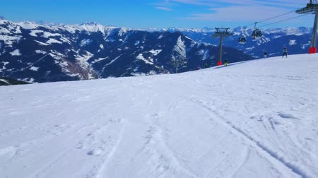 リフト : ZELL AM SEE, AUSTRIA - FEBRUARY 28, 2019: Schmittenhohe mounts gentle slope with groomed piste, covered with chaotic ski prints, leaved by numerous sportsmen, on February 28 in Zell Am See