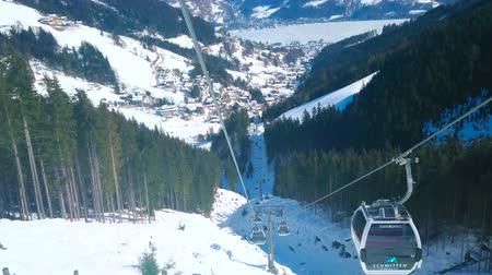 trilhas : ZELL AM SEE, AUSTRIA - FEBRUARY 28, 2019: The cabins of Trassxpress air lift, fast riding along the steep white slope of Schmitten mount, on February 28 in Zell Am See