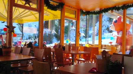 raam : ZELL AM SEE, AUSTRIA - FEBRUARY 28, 2019: Interior of the lounge cafe with riding air tram of Schmittenhohebahn  and fast gondolas of Trassxpress, on February 28 in Zell Am See.
