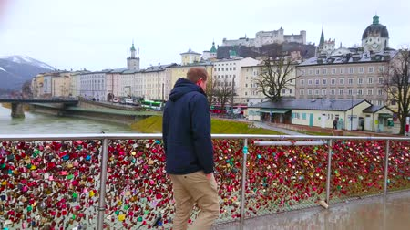 paisagem urbana : SALZBURG, AUSTRIA - MARCH 1, 2019: Rainy cityscape with Hohensalzburg Castle, quarters of old town (Altstadt), embankment of Salzach river, Makartsteg bridge with love padlocks, on March 1 in Salzburg