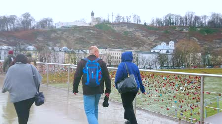 parrocchia : SALZBURG, AUSTRIA - MARCH 1, 2019: People walk the wet Makartsteg bridge with love padlocks on rainy weather, on March 1 in Salzburg Filmati Stock