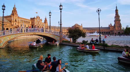 mudejar : SEVILLE, SPAIN - OCTOBER 2, 2019: The small boats, walking people and riding horse-drawn carriages in outstanding Andalusian style Plaza de Espana (Spain Square), on October 2 in Seville