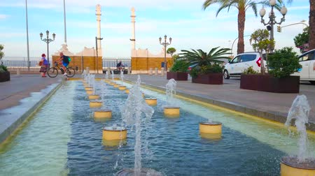 karczma : CADIZ, SPAIN - SEPTEMBER 19, 2019: The fountains in San Juan de Dios square with a view on the Pillars of Hercules, decorating the port gate, on September 19 in Cadiz