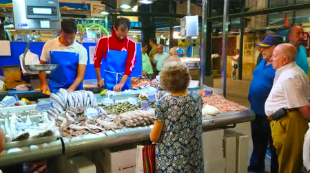 zeedieren : JEREZ, SPANJE - SEPTEMBER 20, 2019: De verkopers knippen en verpakken de verse vis in de kraam van Mercado Central de Abastos (Sentral Abastos-markt), op 20 september in Jerez Stockvideo