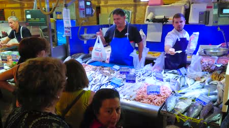 comerciante : JEREZ, SPAIN - SEPTEMBER 20, 2019: The large queue at the fish stall of Mercado Central de Abastos (Sentral Abastos Market), people buy fresh fish and seafood, on September 20 in Jerez